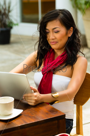 Asian woman is sitting in a bar or cafe outdoor