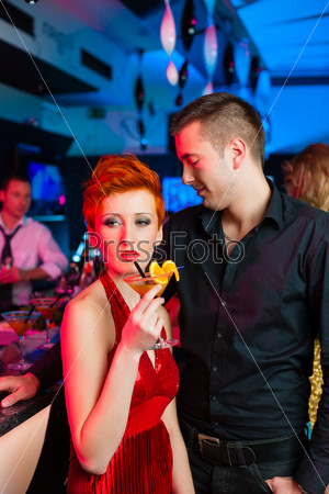 Young couple in bar or club drinking cocktails