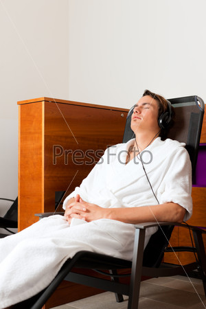 Young man relaxing in spa with music