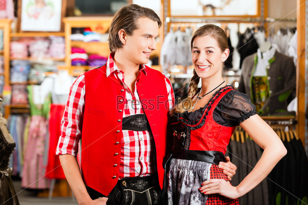 Couple is trying Dirndl or Lederhosen in a shop