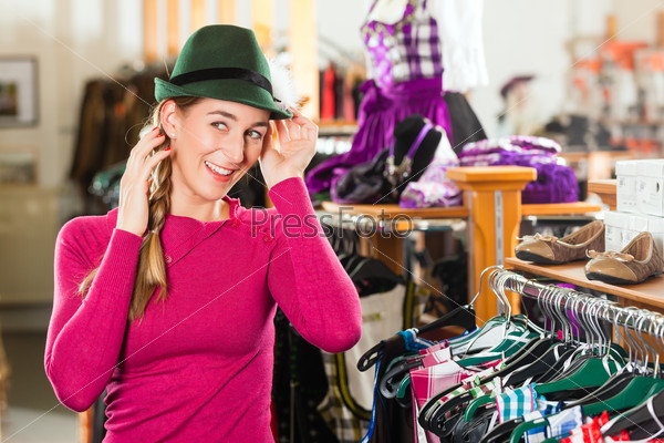 Woman is buying a cap for her Tracht or dirndl in a shop