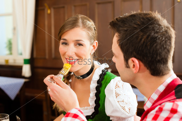 Young couple in traditional Bavarian Tracht eating in restaurant or pub