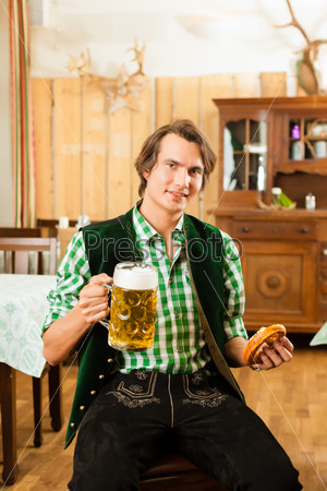 Young man in traditional Bavarian Tracht in restaurant or pub