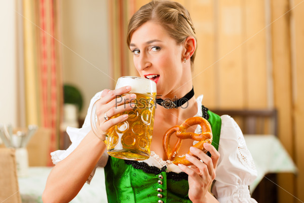 Young woman in traditional Bavarian Tracht in restaurant or pub