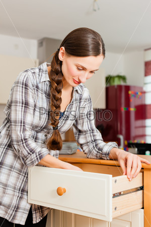 Young woman is assembling a cupboard