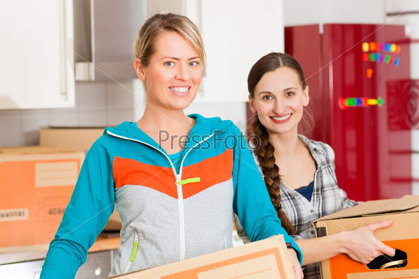 Two woman with moving box in her house