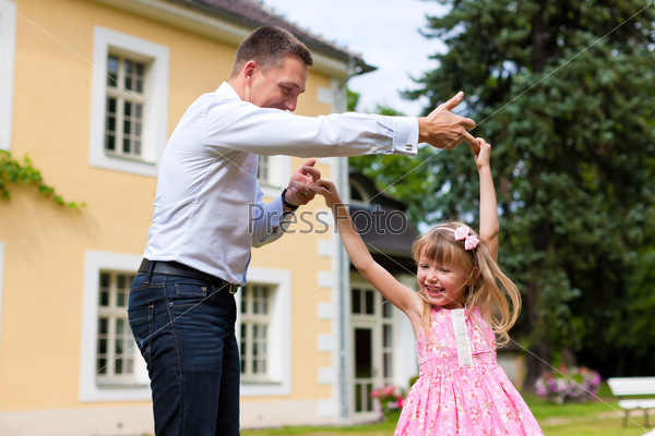 Father is playing with his daughter on a meadow