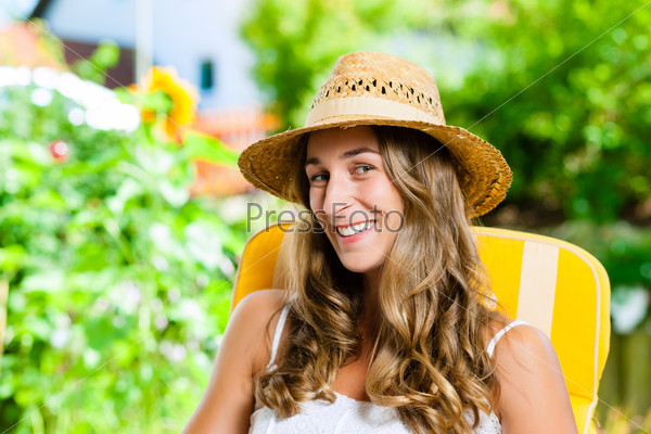 Woman tanning in her garden on lounge chair