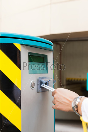 Hand is inserting parking ticket into barrier of garage