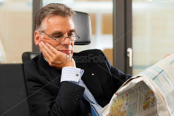 Boss in his office reading newspaper