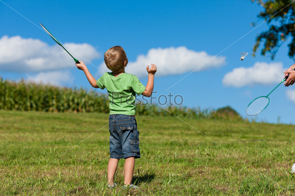 Family - little boy playing badminton outdoors
