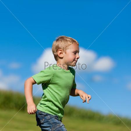 Boy running down a meadow
