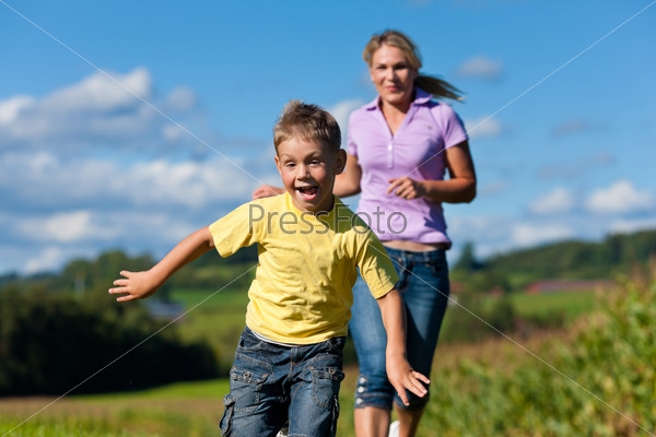Family outdoors is running on a meadow