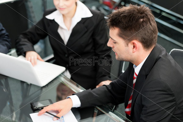 Business people - team meeting in an office with laptop