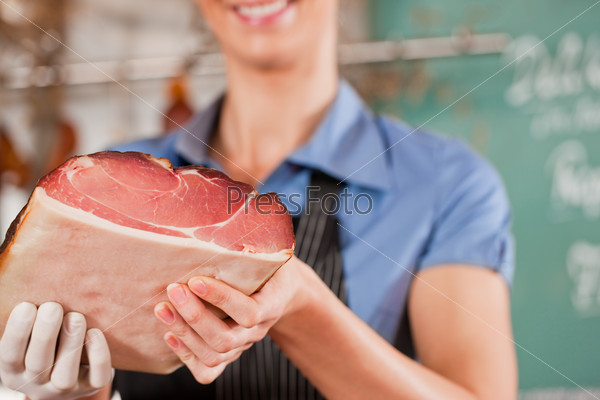 Woman or female butcher with raw ham in butchers shop