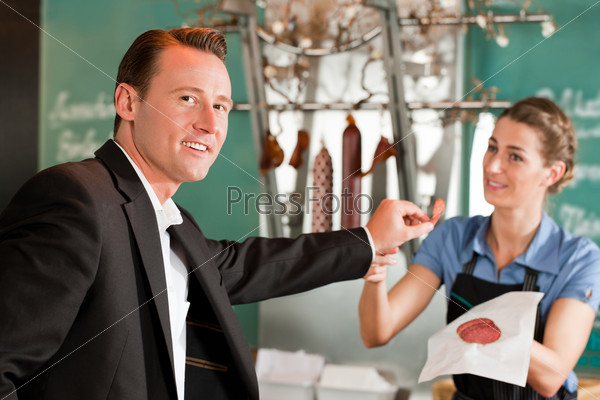 Smiling Male Executive Holding Meat With Butcher