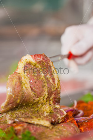 Man working in butchers shop showing meat
