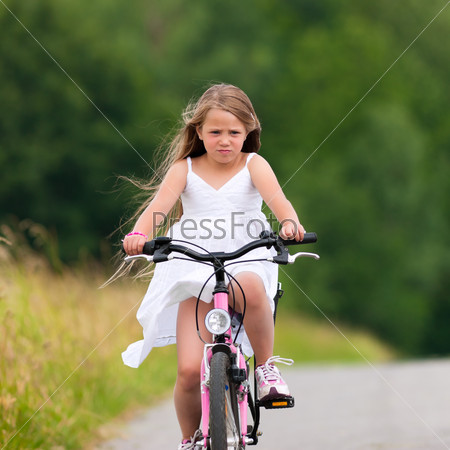 Child cycling outdoors in summer