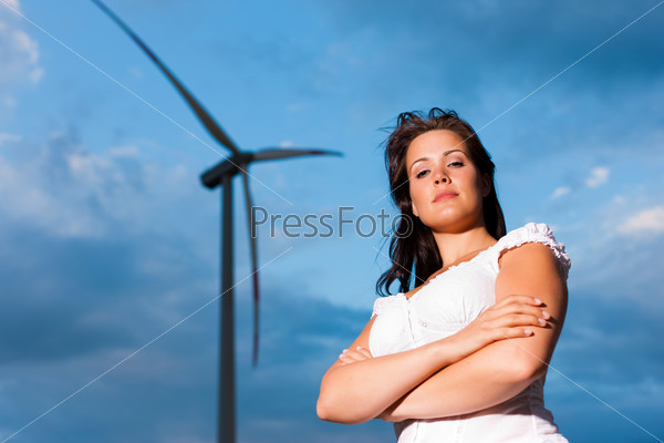 Woman in front of windmill and sky