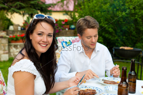 Couple doing BBQ in garden during summer