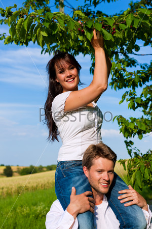 Happy couple eating cherries in summer