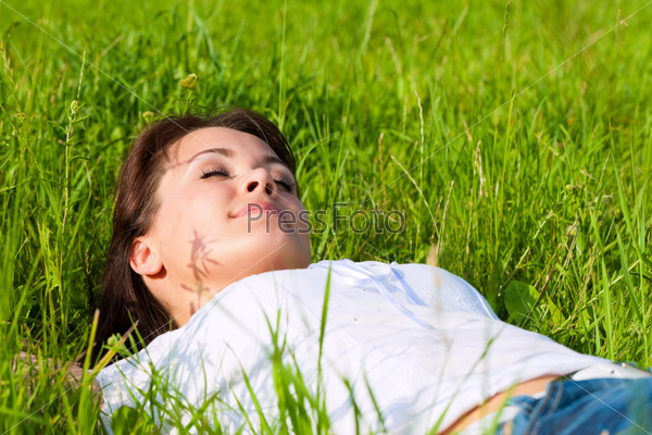 woman laying on a lawn and is dreaming
