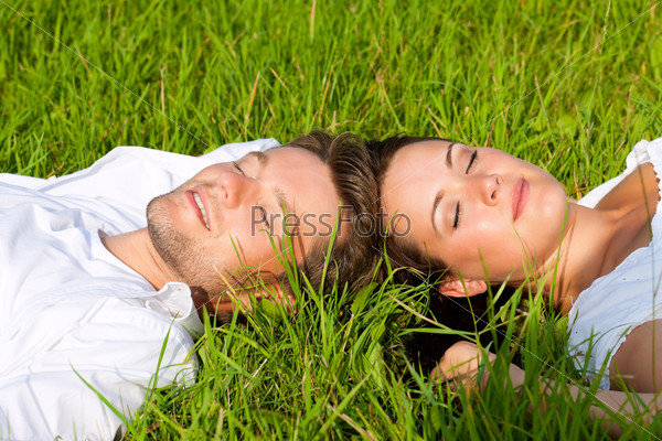 Happy couple lying on a meadow