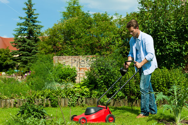 Man is mowing the lawn in summer