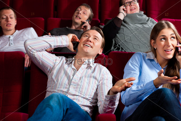 people in cinema theater with mobile phone