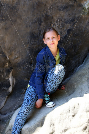 Girl sitting on a rock outdoors