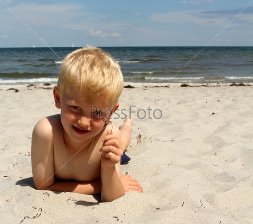 The boy lies on the sea beach