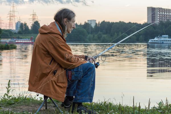 Мужчина рыбачит на удочку на закате