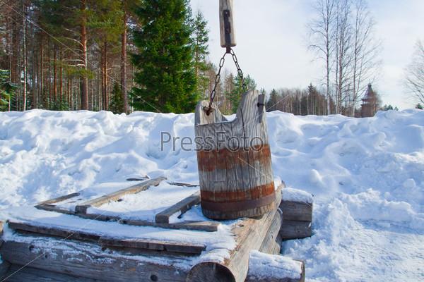 Деревянное ведро стоит на срубе колодца