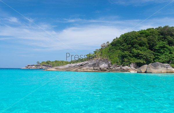 Idyllic tropical blue sea and stone shore