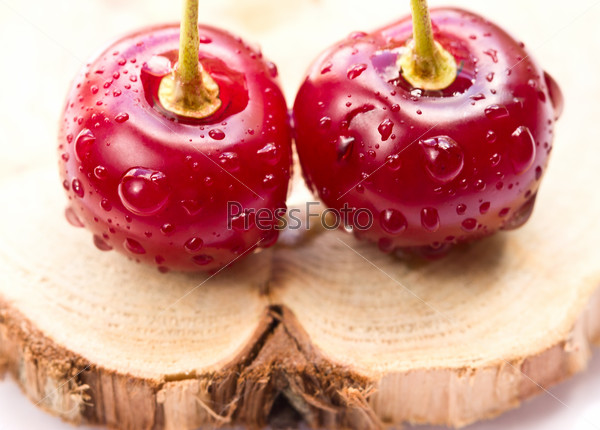 Two cherries on a wooden board