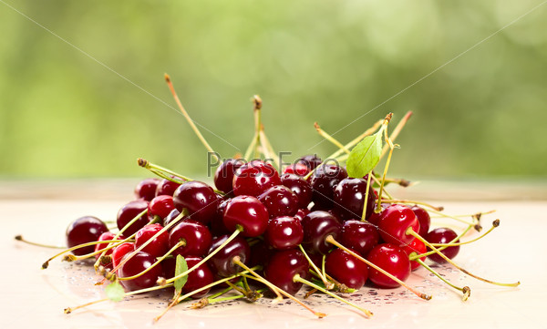 A pile of ripe cherries on a table.