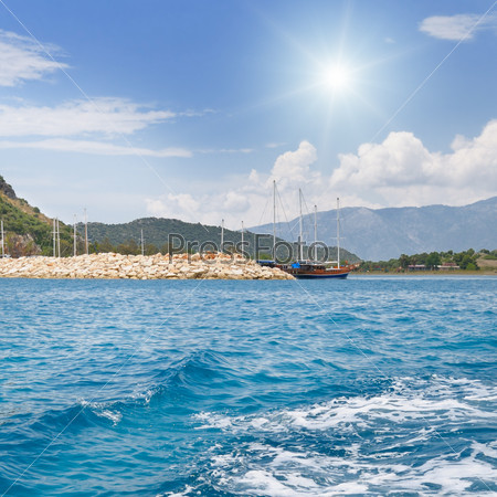 scenic seascape, blue sky, sun, yacht