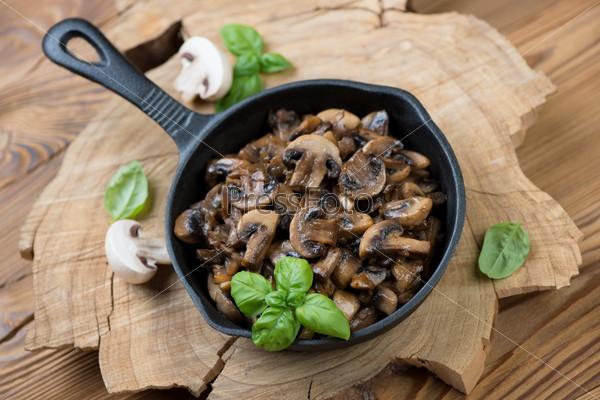 Сковорода с жареными шампиньонами и зеленым базиликом
