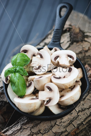 Сковорода с сырыми шампиньонами и зеленым базиликом