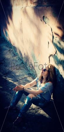 Девушка или женщина возле каменной стены