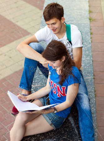 Students or teenagers with notebooks outdoors