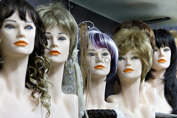 Several female mannequins with wigs