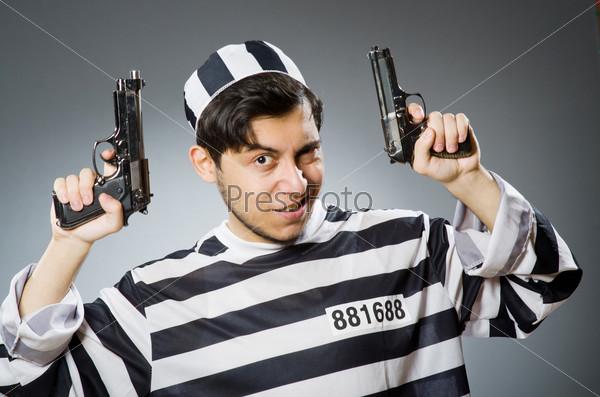 Prisoner with gun against dark background