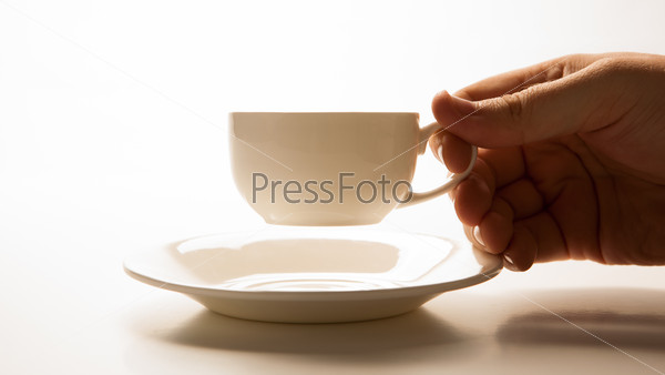 glass cup and saucer in hand closeup