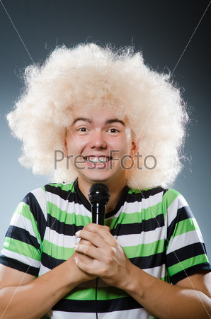 Man in afrowig singing with mic