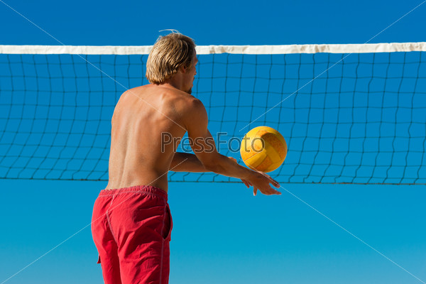 Beach volleyball - man serving the ball