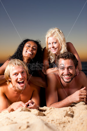 Four friends at the beach with sunset