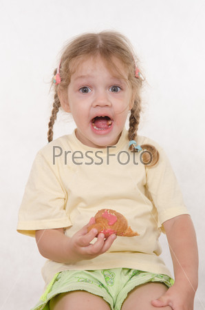 Fun girl opened her mouth while eating a muffin