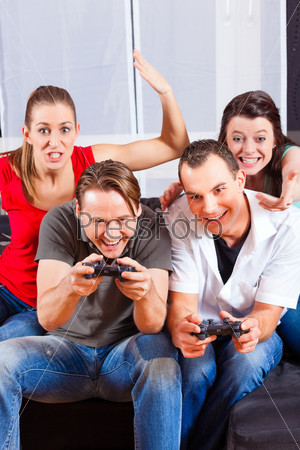 Friends sitting in front of game console box