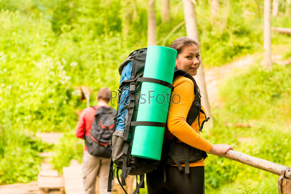 young couple with backpacks in a hike